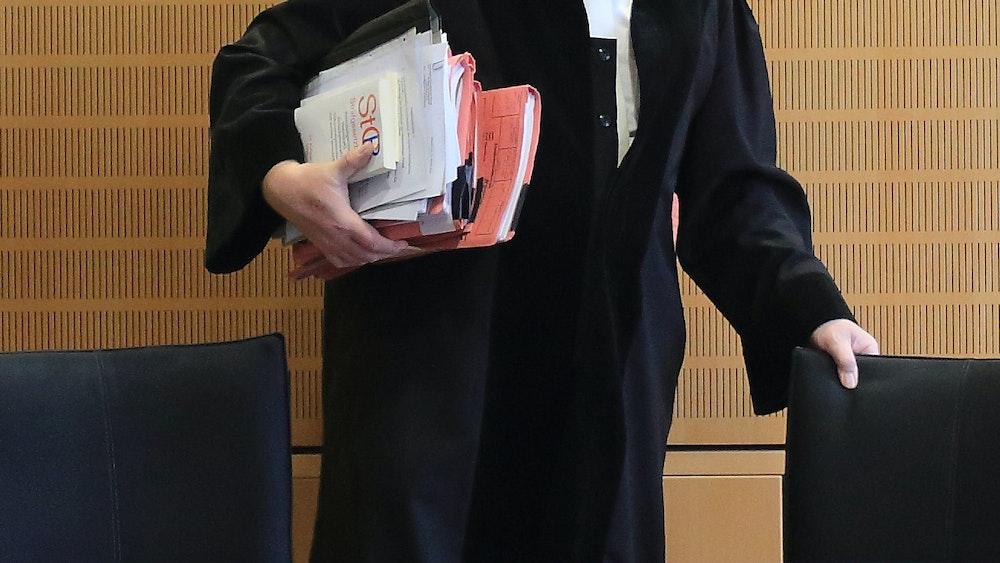 Ein Richter rückt sich zum Auftakt eines Mordprozesses in einem Verhandlungssaal seinen Stuhl zurecht.