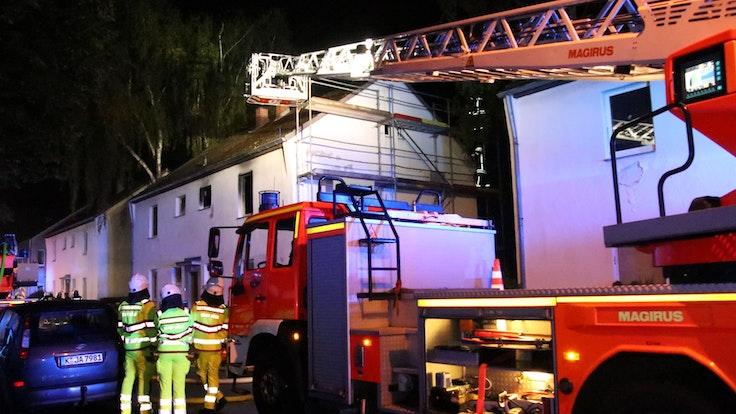 Einsatzkräfte der Feuerwehr sind mit einem Drehleiter-Wagen vor dem Brandhaus.