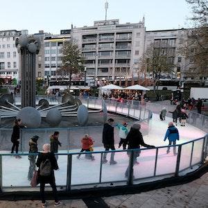 Kinder und Erwachsene laufen auf der Eisbahn am Ebertplatz.