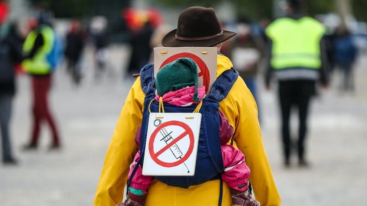Eine Teilnehmerin einer Protestkundgebung der Initiative «Querdenken» trägt am 2. Mai 2020 auf dem Cannstatter Wasen ein Schild gegen Impfungen auf ihrem Rücken.