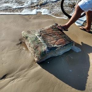 Ein Passant stellt seinen Fuß am Strand von Brasilien auf eine mysteriöse Kiste