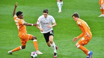 Florian Neuhaus von Borussia Mönchengladbach (Mitte) behauptet den Ball gegen zwei Gegenspieler von Arminia Bielefeld