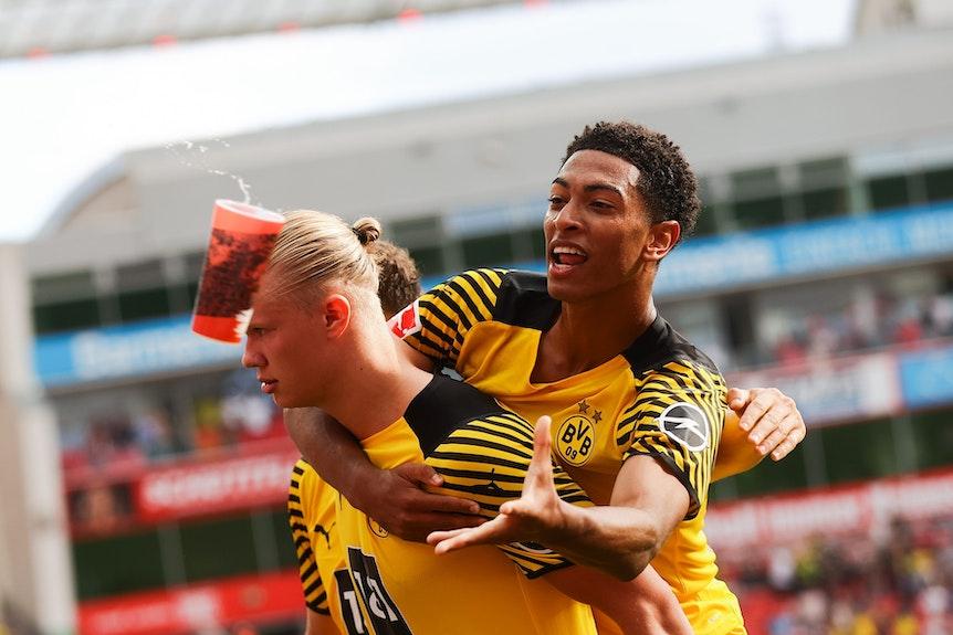Jude Bellingham von Borussia Dortmund fängt beim Torjubel einen Bierbecher