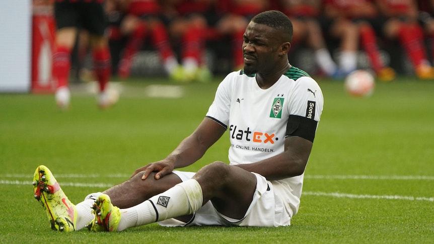 Marcus Thuram von Borussia Mönchengladbach sitzt im Spiel gegen Leverkusen am 21. August 2021 auf dem Boden und hält sich sein verletztes Knie.