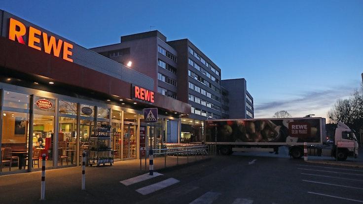 Ein Lkw steht am frühen Morgen vor einem Rewe Supermarkt, der mit Waren beliefert wird. Es ist dunkel, im Hintergrund ist ein Hochhaus zu sehen. Es ist fast menschenleer.