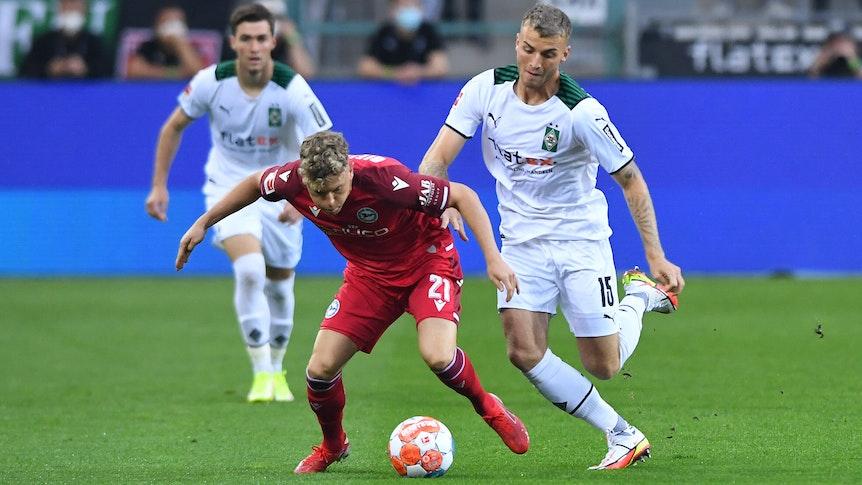 Am Sonntag (12. September 2021) trifft Gladbach im Bundesliga-Duell auf Arminia Bielefeld. Das Foto zeigt Bielefelds Robin Hack (l.) im Duell mit Borussias Jordan Beyer.