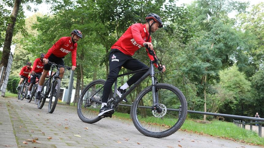 Die Spieler des 1. FC Köln fahren Fahrrad.