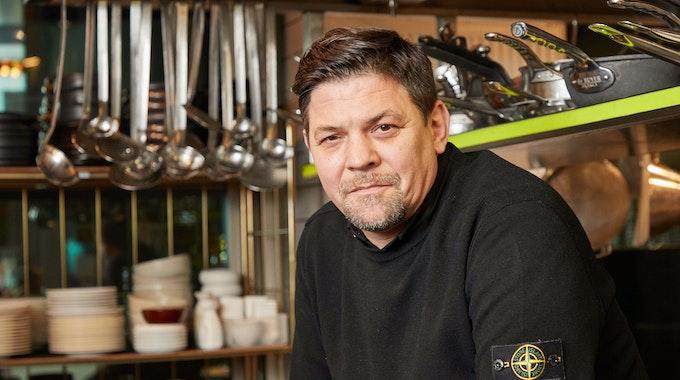 """Fernsehkoch Tim Mälzer sitzt in der Küche seines Restaurants """"Die Gute Botschaft""""."""