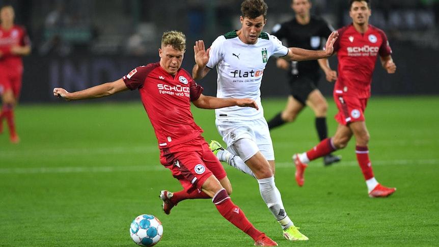 Gladbach-Profi Joe Scally (M.) im Zweikampf mit Bielefelds Robin Hack (l.) beim Bundesliga-Duell zwischen der Borussia und der Arminia am 12. September 2021