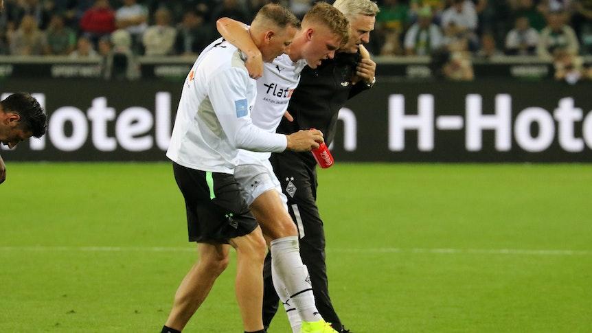 Luca Netz (M.), Spieler von Borussia Mönchengladbach, muss beim Bundesliga-Duell gegen Arminia Bielefeld (12. September 2021) verletzt vom Platz. Physio Dirk Müller (l.) und Team-Arzt Stefan Hertl (r.) stützen den Außenbahnspieler.