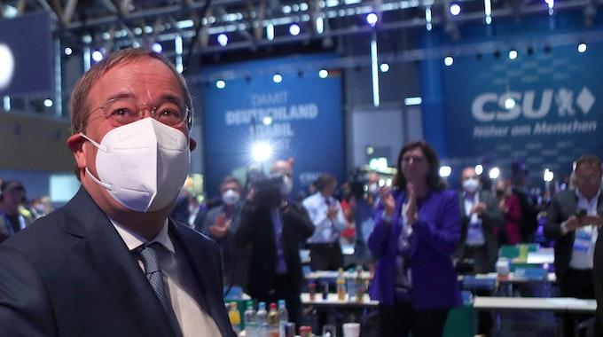 Armin Laschet sitzt mit Mund-Nasen-Schutz beim CSU-Parteitag am Samstag (11. September) in Nürnberg, hinter ihm klatschen die Delegierten.