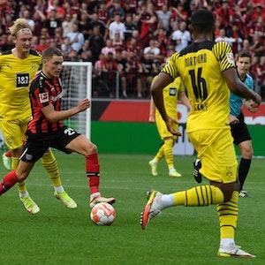 Dortmunds Julian Brandt verfolgt Leverkusens Florian Wirtz.