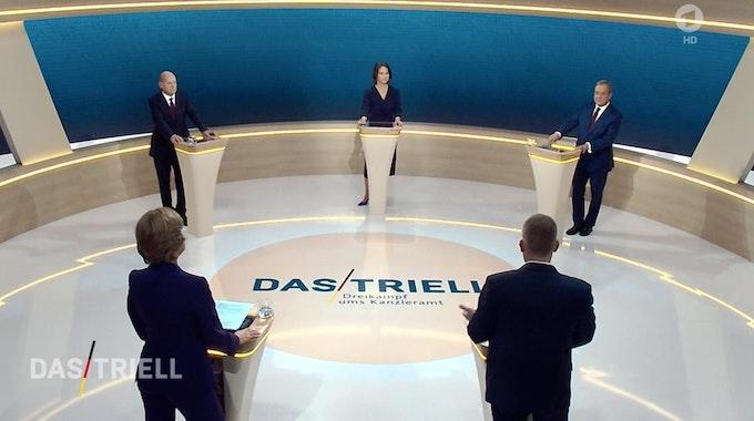 Kanzlerkandidat Olaf Scholz (SPD, hinten, l-r), Kanzlerkandidatin Annalena Baerbock (Bündnis 90/Die Grünen) und Kanzlerkandidat Armin Laschet (CDU) reden miteinander im Fernsehstudio.