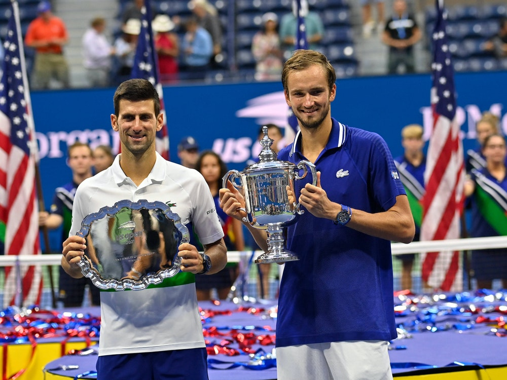 Djokovic und Medwedew posieren mit ihren Trophäen nach der Siegerehrung.