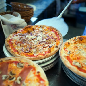 Wer Hunger auf Pizza hat, sollte in NRW bestellen. Das Online-Portal Speisekartenweb.de hat die Preise analysiert. Unser Foto zeigt, wie eine Pizza auf einen Teller geschoben wird.