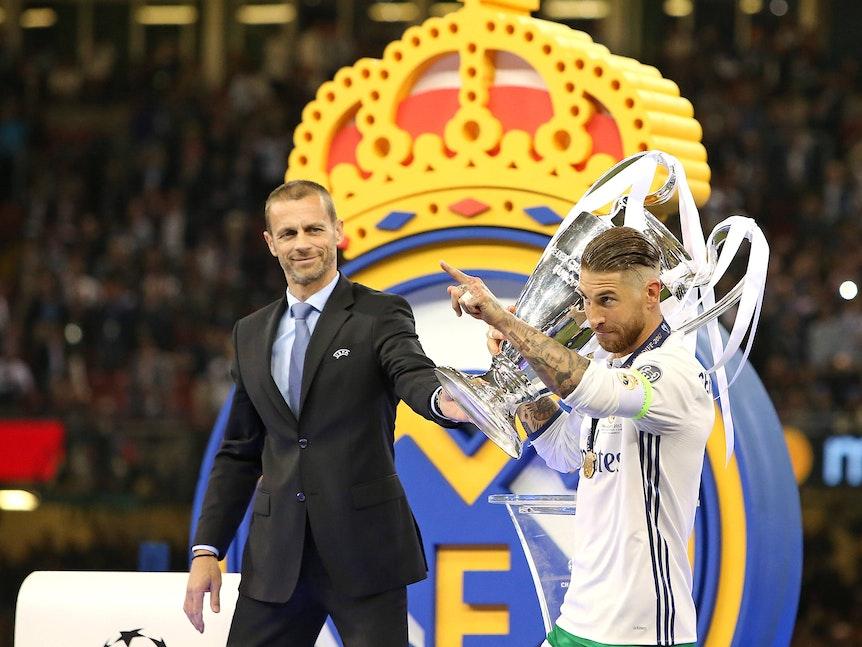 Sergio Ramos hält den Henkelpott in den Händen, im Hintergrund steht Ceferin.