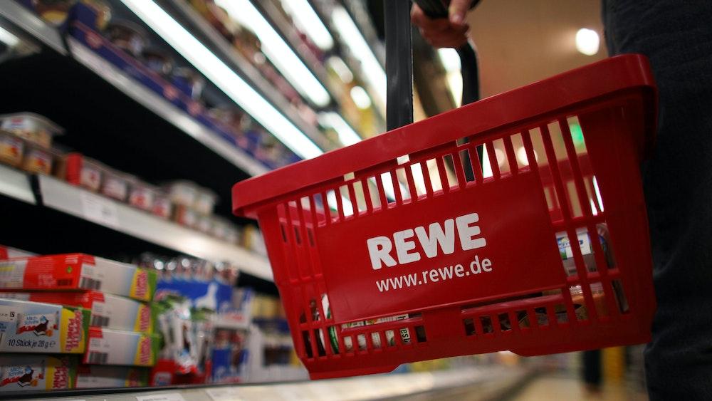 Bei Rewe wird Apfelmark der Firma ODW Lebensmittel GmbH zurückgerufen. Unser Symbolfoto zeigt einen Kunden mit Einkaufskorb vor einem Regal bei Rewe.