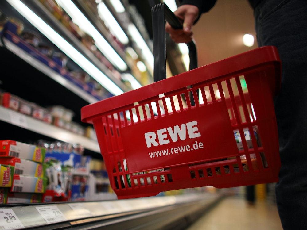 Ein Kunde geht in einem Rewe-Supermarkt mit einem Einkaufskorb am Kühlregal entlang.