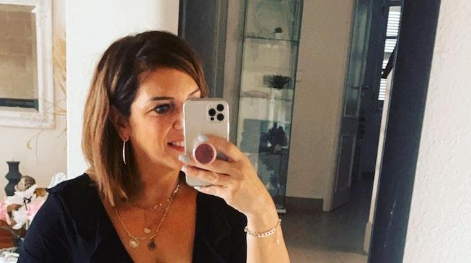 Danni Büchner posiert für ein Selfie lachend vor einem Spiegel.
