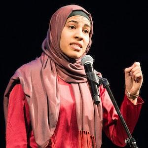 Nemi El-Hassan steht in Braunschweig in einem roten Kleid und mit rotem Kopftuch am Mikrofon auf einer Bühne bei einem Poetry Slam.