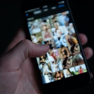 Eine Hand scrollt auf einem Handy herum, auf dem mehrere pornografische Bilder verschwommen zu sehen sind.