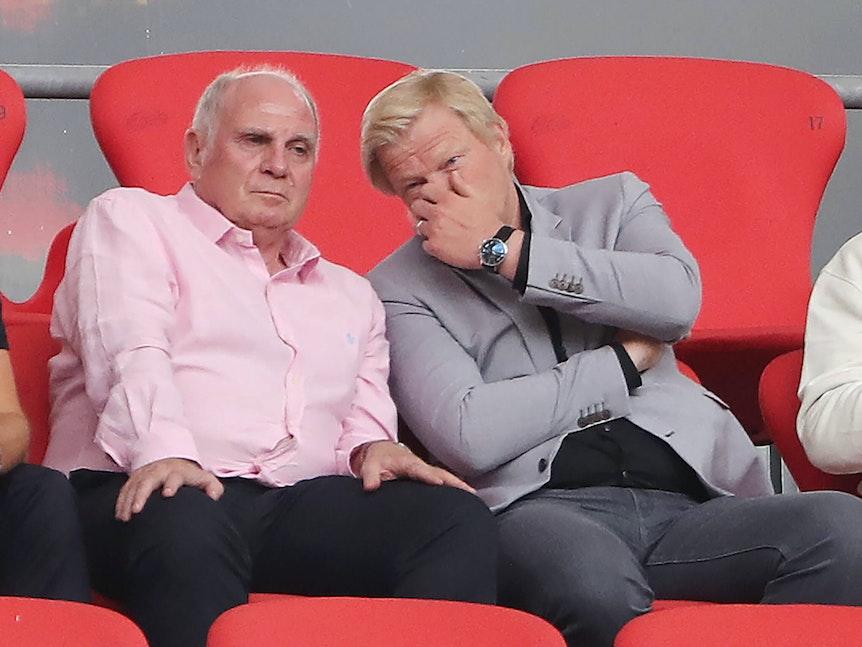 Kahn sitzt neben Hoeneß auf der Tribüne und flüstert ihm etwas ins Ohr.