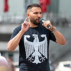 Der Verschwörungsprediger Attila Hildmann spricht im Juli 2020 bei einer Anti-Corona-Demo in Berlin. Er trägt ein schwarzes Shirt mit dem Bundesadler.