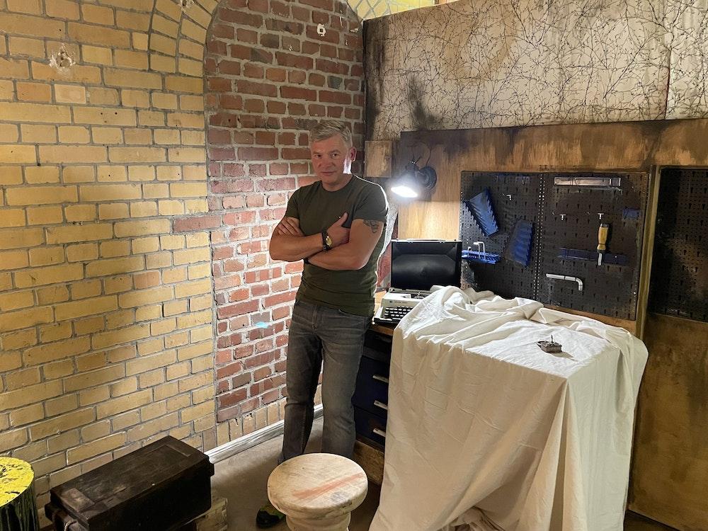Bestseller-Autor Andreas Winkelmann steht im Escape Room an eine Werkbank angelehnt.