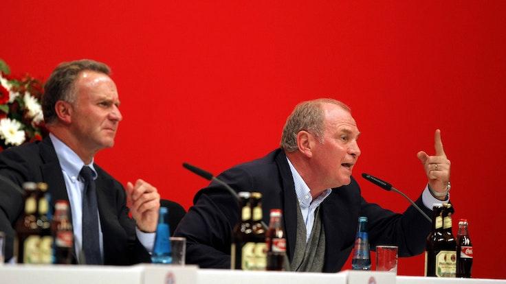 Rummenigge sitzt links neben dem wütenden Hoeneß auf der Bühne bei der Jahreshauptversammlung im Jahr 2007.