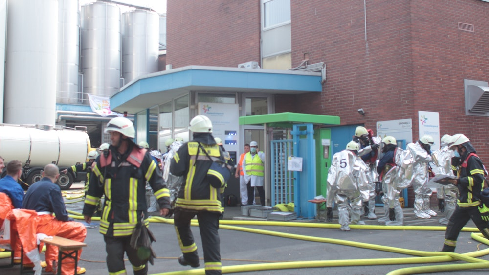 Feuerwehrmänner und Männer in Spezialanzügen befinden sich vor einem Werk.