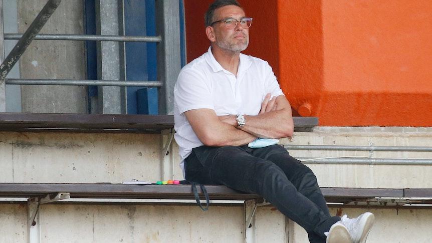 Uwe Kamps, Torwarttrainer von Borussia Mönchengladbach, beobachtet am 21. August 2021 im Rheydter Grenzlandstadion das Regionalliga-Spiel zwischen Borussias U23 und Preußen Münster. Kamps sitzt auf der Tribüne und schaut nach vorne.