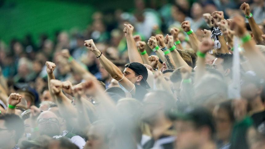 Fans von Borussia Mönchengladbach beim Bundesliga-Duell am 12. September 2021 gegen Arminia Bielefeld im Borussia-Park. Zahlreiche Fans strecken ihre Arme nach oben.