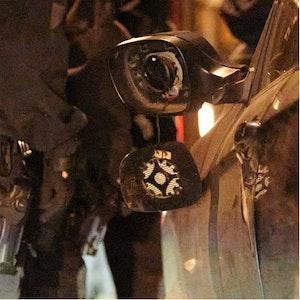 Ein zerstörter Autospiegel hängt an einem Pkw.