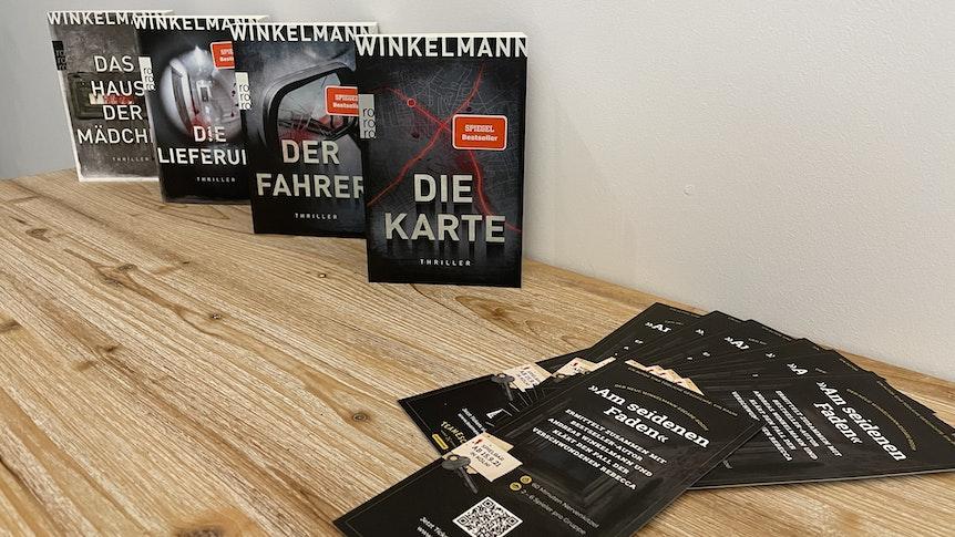 Die vier Bücher der Thriller-Reihe von Andreas Winkelmann stehen auf einem Tisch, davor liegen Flyer zum neuen Escape Room.