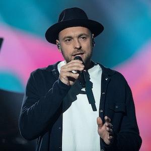Max Mutzke singt auf einer Benefizgala im schwarzen Anzug.