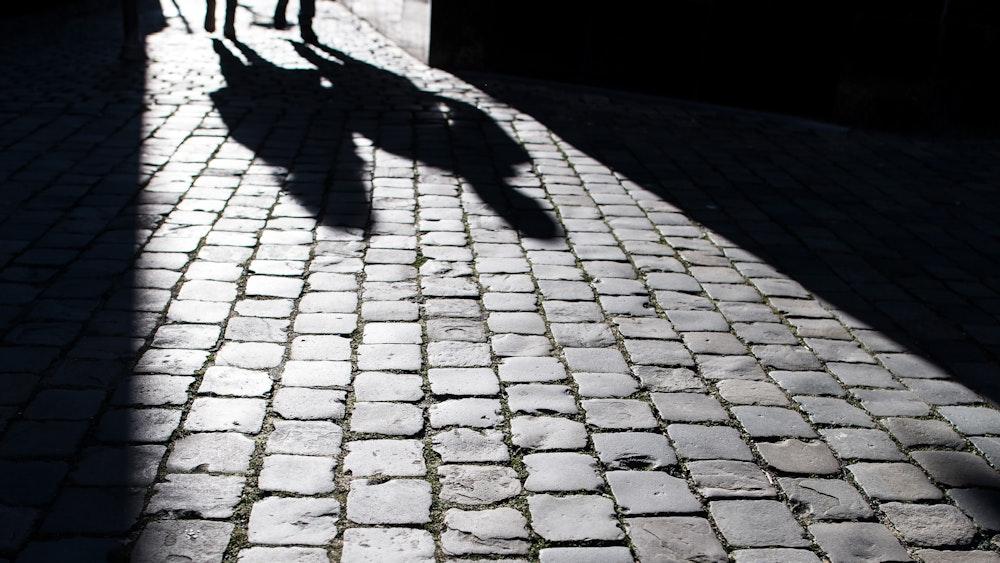 Fußgänger werfen am 21. Januar 2019 in der Aachener Innenstadt ihre Schatten auf das Pflaster.