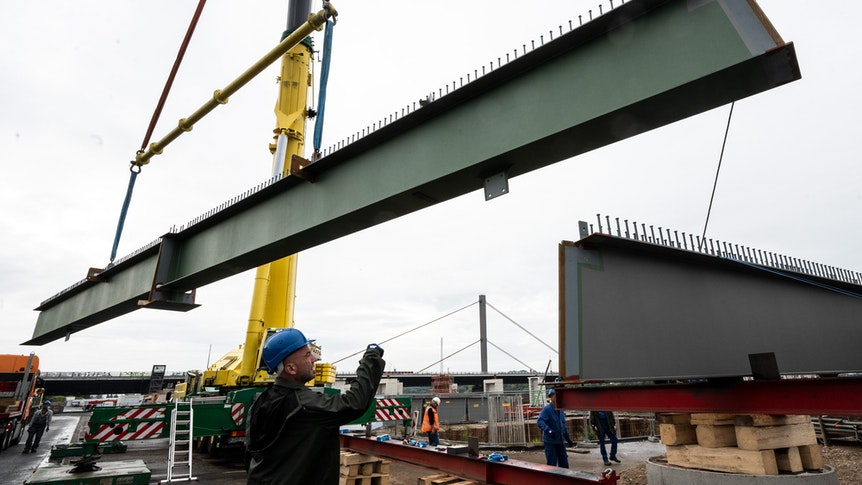 15.09.2021, Nordrhein-Westfalen, Leverkusen: Querträger aus Stahl für die neue Rheinbrücke werden mit einem Kran in Position gebracht.+