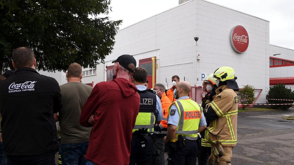 Polizei, Feuerwehr und Coca-Cola-Mitarbeiter stehen vor dem Werk in Köln-Ossendorf.