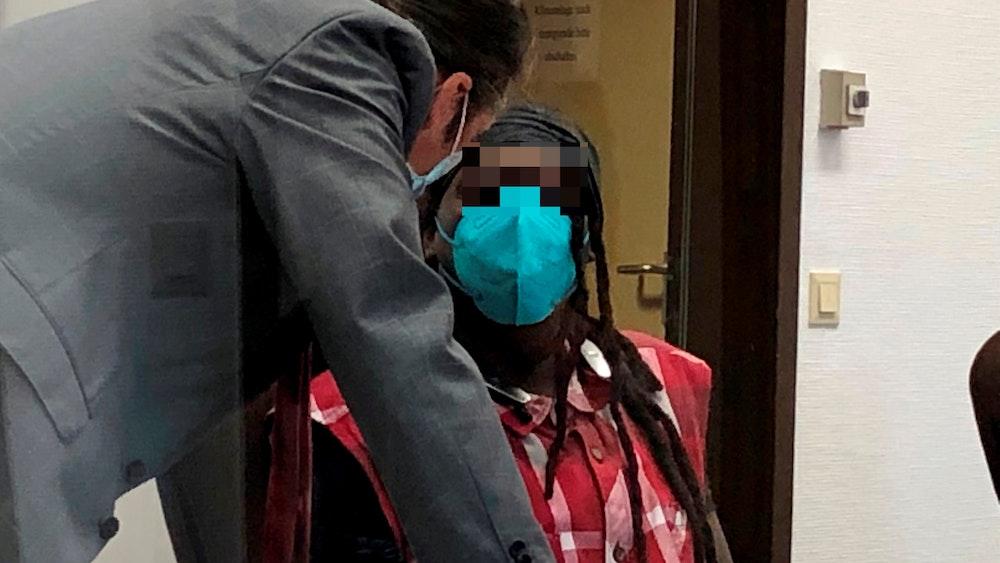Ein Mann sitzt auf der Anklagebank, sein Verteidiger beugt sich zu ihm runter.