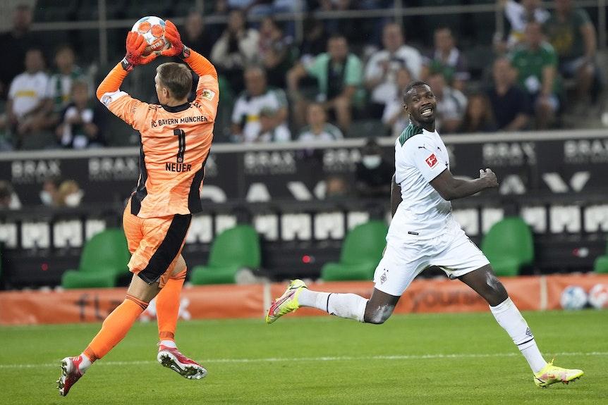 Manuel Neuer hat den Ball vor Marcus Thuram