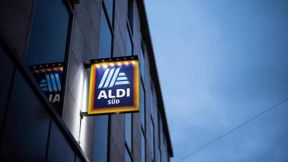 Das Logo einer Aldi Süd Filiale, fotografiert in einer Fußgängerzone der Düsseldorfer Innenstadt, ist beleuchtet am Abend zu sehen.