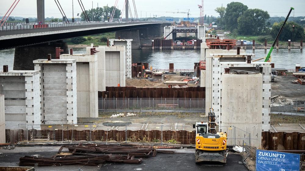 Autos fahren am 145. September 2021 an der Baustelle für die neue Rheinbrücke vorbei. Am Neubau der Leverkusener Rheinbrücke werden mit mehreren Schwertransporten die ersten Stahlbauteile angeliefert. Insgesamt handele es sich um mehr als 1000 Tonnen Stahl, die die Brücke erreichten, teilte die Autobahn GmbH des Bundes mit.