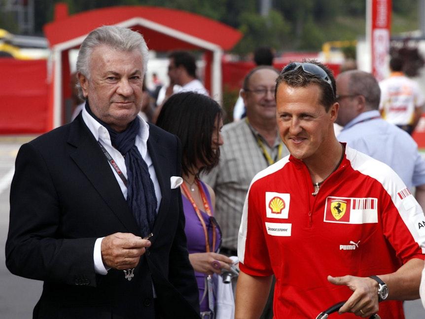 Willi Weber und Michael Schumacher sprechen miteinander.