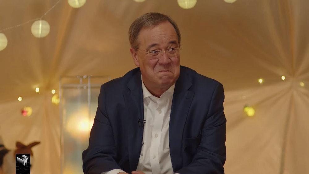 Armin Laschet sitzt im Zelt mit den beiden Kinderreportern Pauline und Romeo und verzieht erstaunt sein Gesicht.