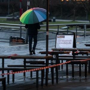 Ein Passant geht unter einem bunten Regenschirm an der Uferprommenade des Phoenix Sees an den wegen der Corona-Pandemie gesperrten Tischen vor einer Bäckerei vorbei.