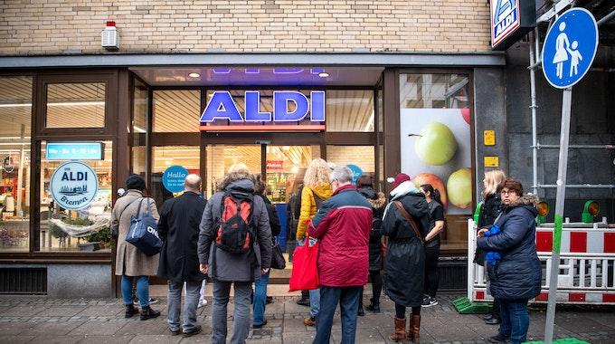 Kunden stehen am frühen Morgen kurz vor Öffnung vor einem Aldi-Markt.