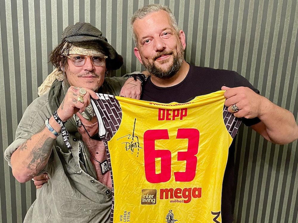 Johnny Depp und der in Suhl lebende Musiker Alexander Becker halten zusammen ein Trikot des Volleyball-Bundesligistes VfB Suhl.