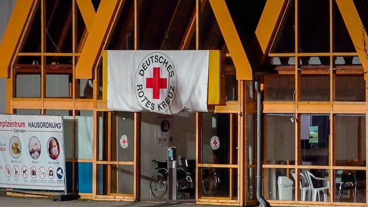 Eine Rot-Kreuz-Fahne hängt über dem Eingang zum Impfzentrum in Eich. Im sächsischen Vogtlandkreis hat es einen Brandanschlag auf ein Impfzentrum gegeben.