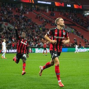 Leverkusens Torschütze Florian Wirtz (M) jubelt nach seinem Treffer zur 2:1 Führung. Daneben laufen Jeremie Frimpong (l) und Moussa Diaby.