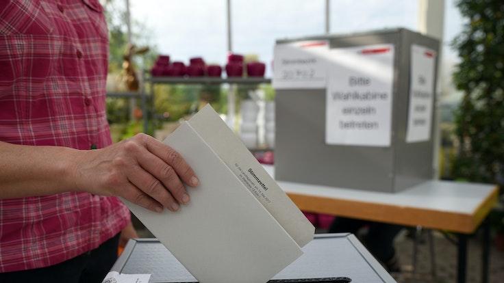 Eine Wählerin wirft in einem Wahllokal in einer Gärtnerei in Köln ihren Stimmzettel zur Landtagswahl in NRW in die Wahlurne.